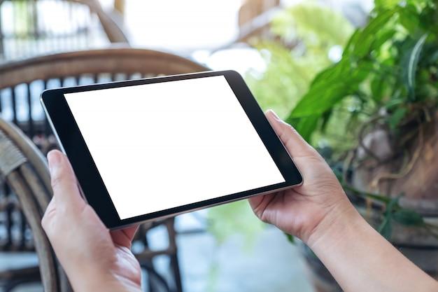 Mains Tenant Et à L'aide De Tablet Pc Noir Avec écran De Bureau Blanc Vierge Alors Qu'il était Assis à L'extérieur Photo Premium
