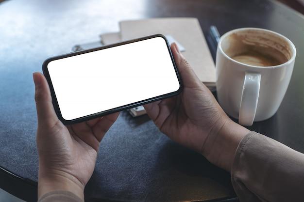 Mains Tenant Et à L'aide D'un Téléphone Mobile Noir Avec écran Blanc Horizontalement Pour Regarder Avec Une Tasse De Café Et Des Cahiers Sur La Table Photo Premium