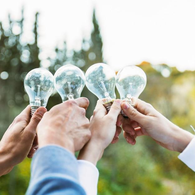 Mains tenant des ampoules le jour de l'écologie Photo gratuit
