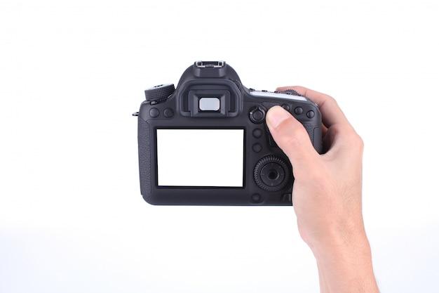 Mains tenant l'appareil photo reflex numérique sur fond blanc Photo Premium