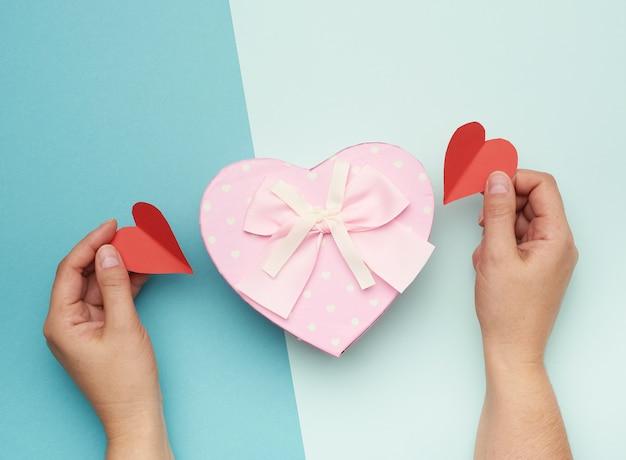 Mains Tenant Une Boîte En Carton Rose Avec Un Arc Photo Premium