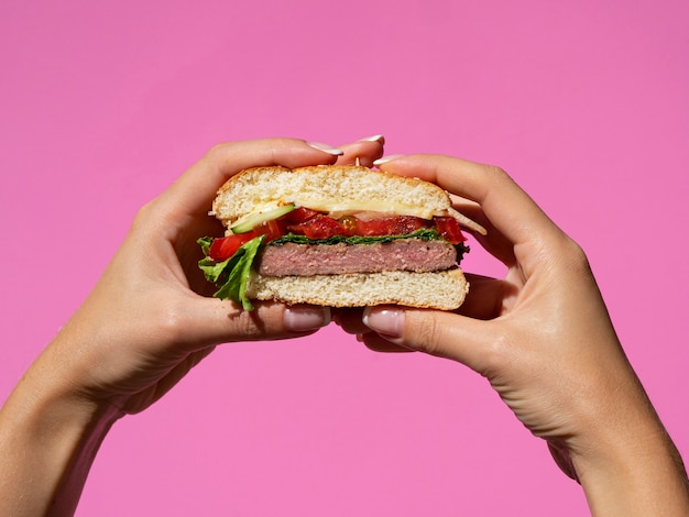 Mains tenant un burger savoureux américain Photo gratuit