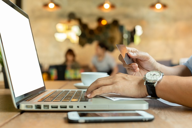 Mains tenant la carte de crédit et à l'aide du clavier portable sur la table. Photo Premium