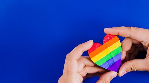 Mains tenant un coeur avec les couleurs du drapeau de la fierté Photo gratuit