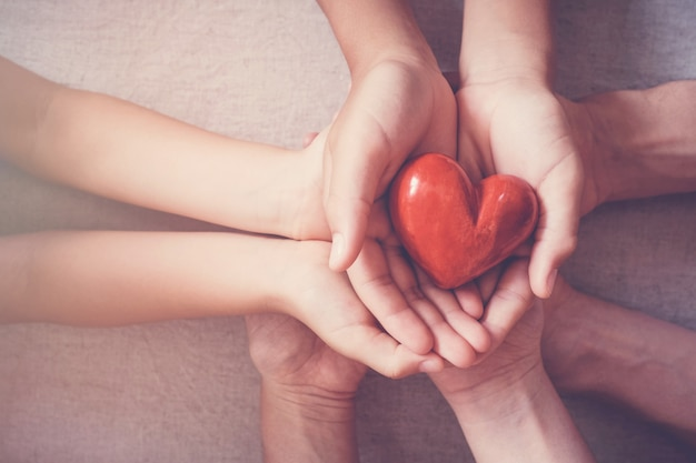 Mains tenant coeur rouge, assurance maladie, notion de don Photo Premium