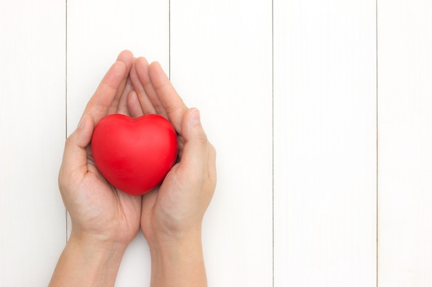 Mains tenant coeur rouge, soins de santé, concept d'assurance. donner de l'amour pour la saint-valentin. Photo Premium