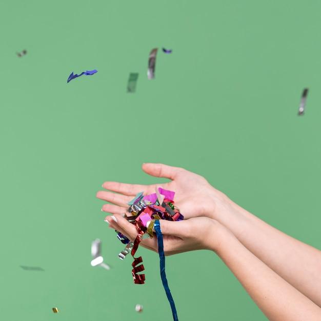 Mains tenant des confettis sur fond vert Photo gratuit