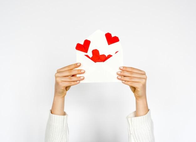 Mains tenant l'enveloppe avec des coeurs à l'intérieur sur fond blanc Photo gratuit