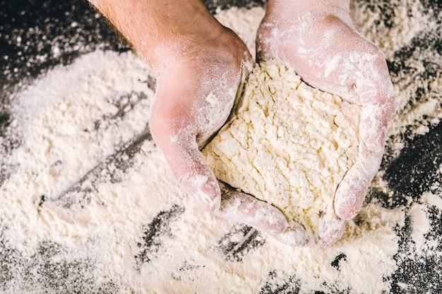 Mains tenant de la farine de blé blanche Photo Premium