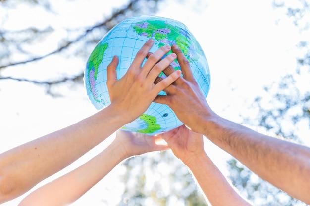 Mains tenant un globe gonflable Photo gratuit