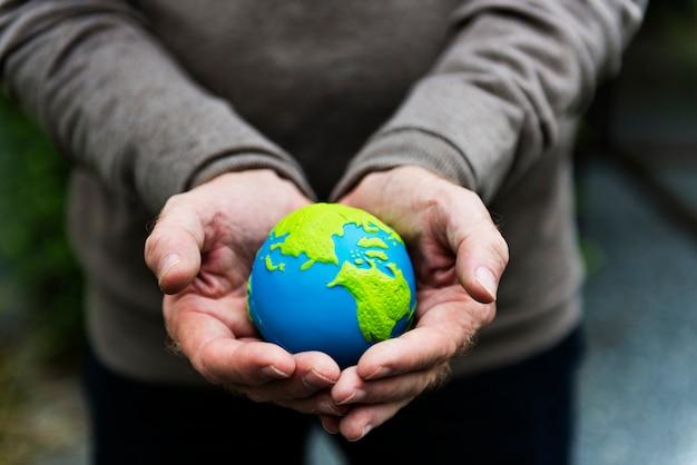 Mains tenant un globe terrestre en terre cuite Photo gratuit