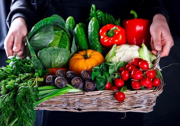 Mains tenant le grand panier avec différents légumes frais de la ferme. Photo Premium