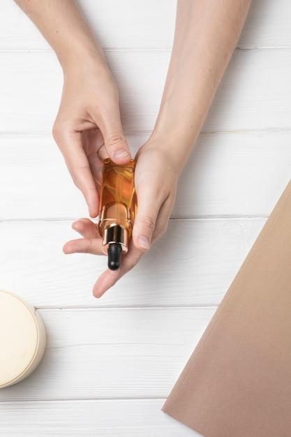 Mains tenant de l'huile corporelle sur un fond en bois blanc Photo gratuit