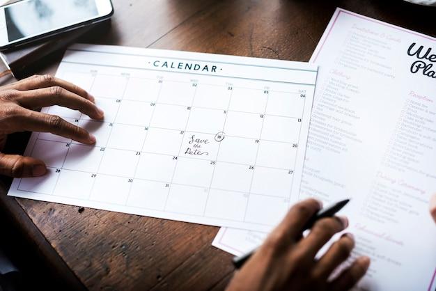 Mains tenant la liste de contrôle de planification de mariage information préparation Photo Premium
