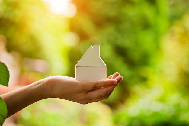 Mains tenant le modèle de maison en bois. achat d'un nouveau concept d'assurance habitation et habitation. Photo Premium