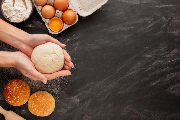 Mains Tenant La Pâte Avec Des Oeufs Et De La Farine Photo gratuit