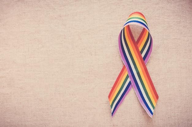 Mains tenant un ruban arc-en-ciel de fierté gay pour la sensibilisation des lgbt Photo Premium