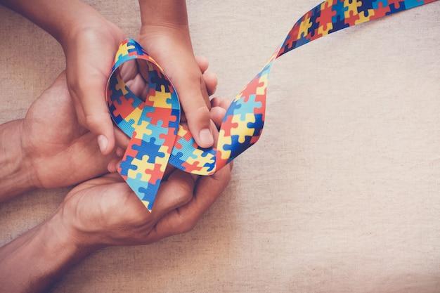 Mains tenant un ruban de puzzle pour la sensibilisation à l'autisme Photo Premium
