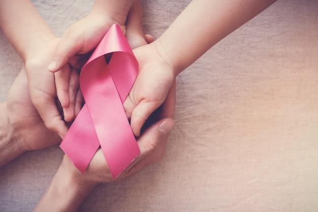Mains tenant un ruban rose, sensibilisation au cancer du sein en octobre Photo Premium