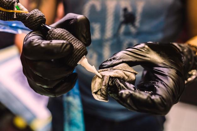 Mains tenant le stylo de tatouage Photo gratuit