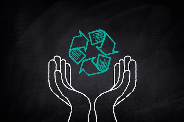 Mains tenant un symbole de recyclage sur un tableau noir Photo gratuit