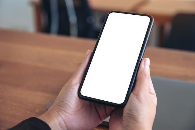 Mains Tenant Un Téléphone Mobile Noir Avec écran Blanc Vierge Avec Ordinateur Portable Sur Table En Bois Photo Premium