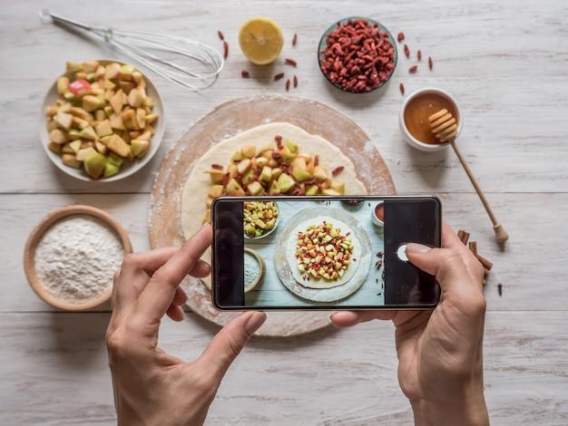Mains Tenant Téléphone Photo De Nourriture. Tarte Aux Pommes Pour Les Vacances. Tarte Aux Baies De Goji Et Aux Pommes. Photo Premium