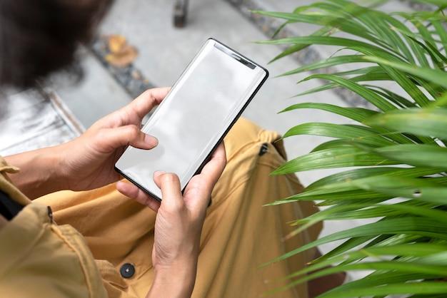 Mains tenant et en utilisant un téléphone portable avec écran blanc dans le jardin. Photo Premium