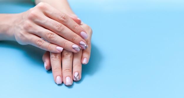 Mains tendres avec manucure nude parfaite sur bleu pastel Photo Premium