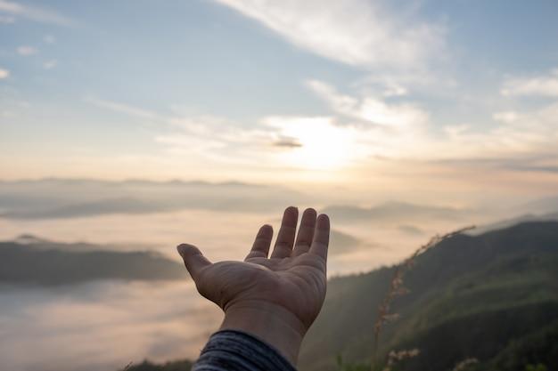 Mains tendues pour recevoir la lumière naturelle et une vue sur la montagne Photo Premium
