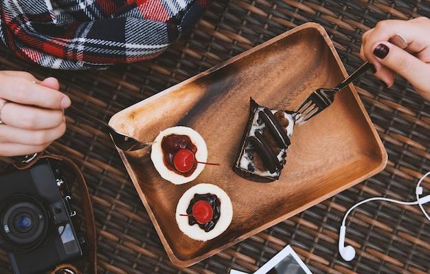 Mains tenir fourches manger des gâteaux sucrés Photo gratuit