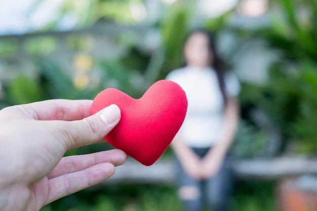 Les mains tiennent un coeur rouge le soir pour remplacer l'amour de la saint-valentin. Photo Premium