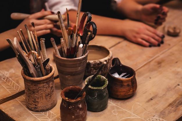 Mains Travaillant Et Finissant La Sculpture Avec De L'argile Sur Une Table En Bois En Atelier Photo Premium