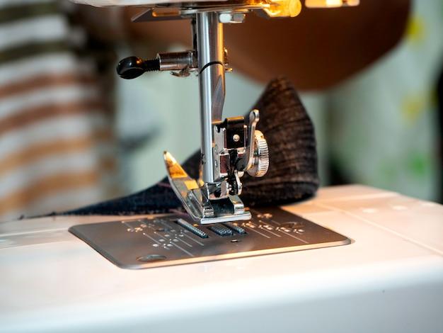 Mains travaillant sur la machine à coudre Photo Premium