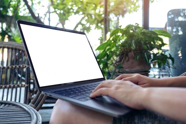 Mains En Utilisant Et En Tapant Sur Un Ordinateur Portable Avec Un écran De Bureau Blanc Vierge Alors Qu'il était Assis à L'extérieur Photo Premium