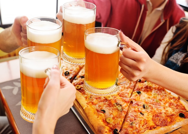 Mains avec des verres de bière close-up sur un fond de pizza. Photo Premium