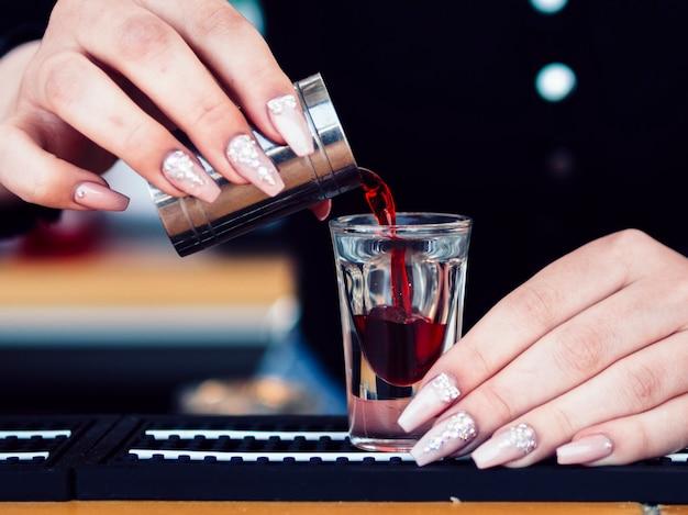 Mains verser une boisson alcoolisée rouge en verre Photo gratuit