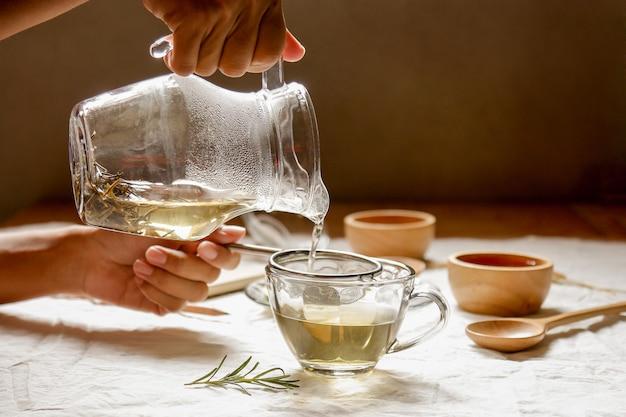 Mains verser de l'eau chaude dans un verre pour faire du thé au romarin Photo Premium