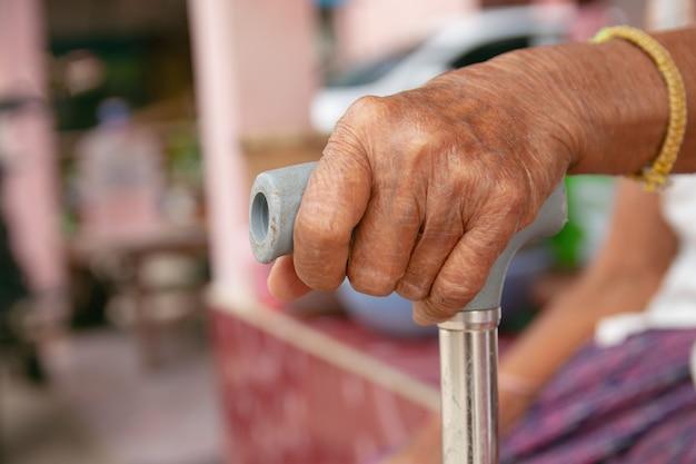 Mains de vieille femme en asie avec une canne Photo Premium