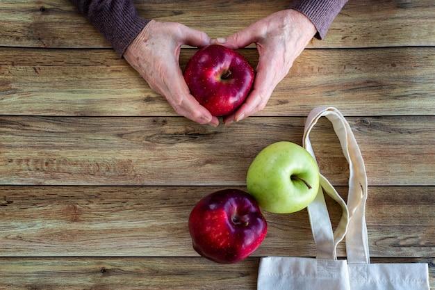 Mains d'une vieille femme tenant une pomme bio fraîche. sac shopping écologique sur fond en bois Photo Premium