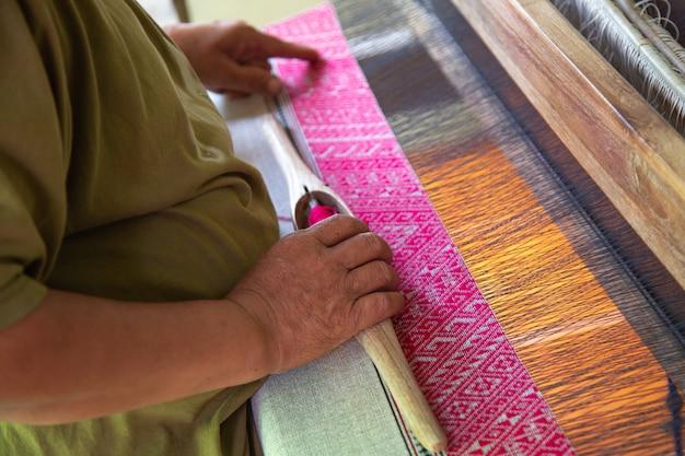 Les mains de la vieille femme en train de tisser, l'ancienne méthode de tissage. Photo Premium