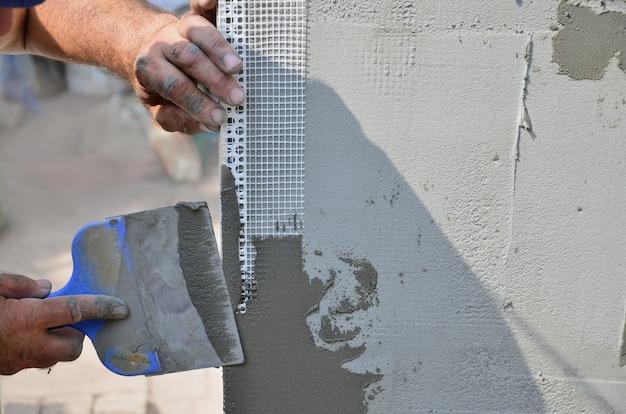 Mains, vieux, ouvrier, mur, plâtrage, outils, rénover, maison Photo Premium