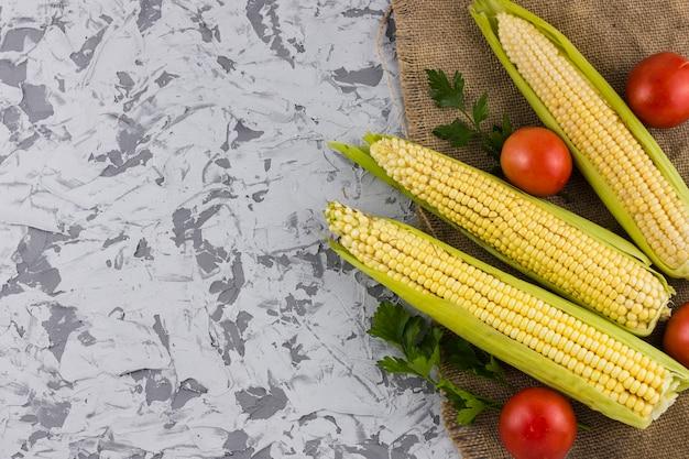 Maïs frais et tomates avec espace de copie Photo gratuit