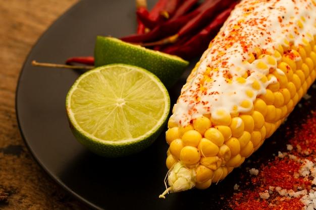 Maïs sur plaque avec des citrons verts Photo gratuit