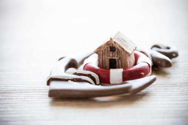 Maison sur ancre de bouée de sauvetage rouge sur bois Photo Premium