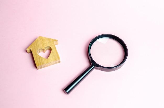 Maison en bois avec un coeur et une loupe Photo Premium