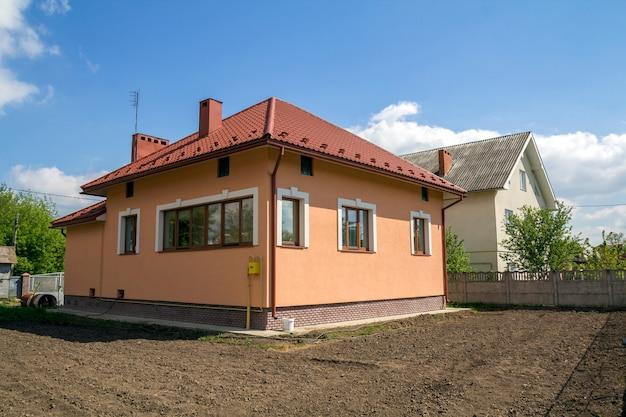 Maison de campagne neuve à un magasin avec toit en tuiles rouges, fenêtres en plastique, murs en plâtre et hautes cheminées Photo Premium