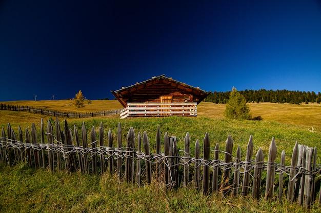 Maison Dans Un Champ Herbeux Avec Une Clôture En Bois En Dolomite Italie Photo gratuit