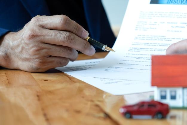 La maison du courtier tient un stylo pointant vers le document. Photo Premium
