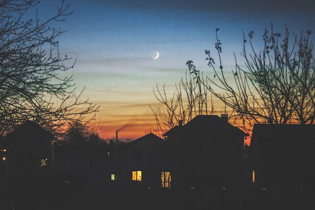 Maison du soir à l'ombre et au jeune mois. Photo Premium